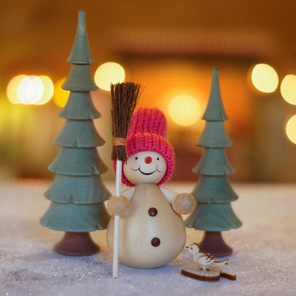 Schneemann mit Besen im Wald